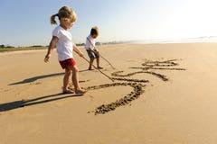 Miúdos que escrevem na areia Fotografia de Stock