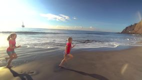 Miúdos que funcionam ao longo da praia video estoque