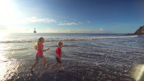 Miúdos que funcionam ao longo da praia vídeos de arquivo