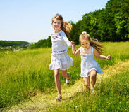 Miúdos que funcionam através da grama verde ao ar livre. Imagens de Stock Royalty Free