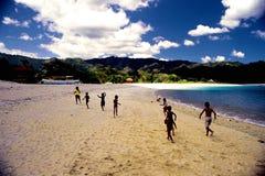 Miúdos que funcionam na praia Imagem de Stock