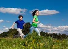 Miúdos que funcionam, salto ao ar livre Fotos de Stock