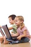 Miúdos que jogam em portáteis imagens de stock