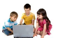 Miúdos que jogam em um computador portátil fotografia de stock