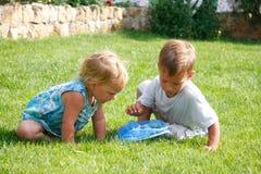 Miúdos que jogam na grama verde Imagem de Stock