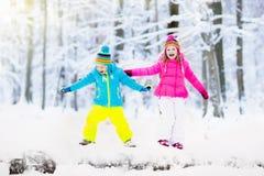 Miúdos que jogam na neve Jogo de crianças fora na queda de neve do inverno Imagens de Stock Royalty Free
