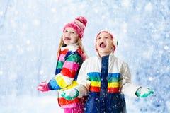 Miúdos que jogam na neve Jogo de crianças fora na queda de neve do inverno Fotos de Stock Royalty Free