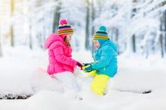 Miúdos que jogam na neve Jogo de crianças fora na queda de neve do inverno Fotos de Stock