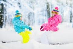 Miúdos que jogam na neve Jogo de crianças fora na queda de neve do inverno Imagem de Stock Royalty Free