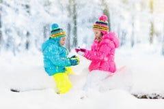 Miúdos que jogam na neve Jogo de crianças fora na queda de neve do inverno Imagem de Stock