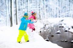 Miúdos que jogam na neve Jogo de crianças fora na queda de neve do inverno Fotografia de Stock