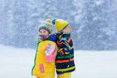 Miúdos que jogam na neve Jogo de crianças no inverno fotografia de stock royalty free