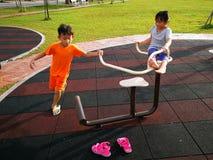 Miúdos que jogam no campo de jogos Foto de Stock Royalty Free