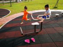 Miúdos que jogam no campo de jogos Imagem de Stock