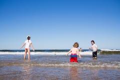 Miúdos que jogam no mar Imagem de Stock