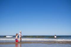 Miúdos que jogam no mar Fotografia de Stock Royalty Free