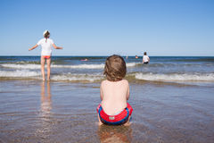 Miúdos que jogam no mar Foto de Stock