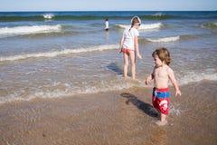Miúdos que jogam no mar Fotografia de Stock