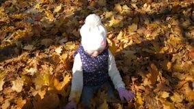 Miúdos que jogam no parque do outono Uma menina encontra-se em uma pilha das folhas amarelas, folhas derrama para baixo sobre ela filme