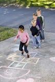 Miúdos que jogam o hopscotch Fotos de Stock