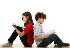 Miúdos que lêem em casa Fotos de Stock Royalty Free
