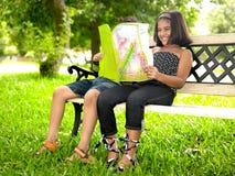 Miúdos que lêem um livro em um parque Fotografia de Stock Royalty Free