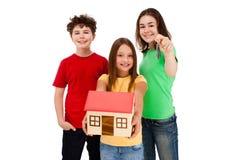 Miúdos que mantêm o modelo da casa isolado no branco Imagens de Stock Royalty Free