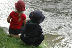 Miúdos que olham o rio foto de stock