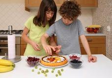 Miúdos que preparam o bolo fruity imagens de stock royalty free