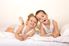 Miúdos que têm o divertimento na cama foto de stock royalty free