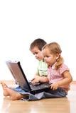 Miúdos que usam portáteis imagens de stock