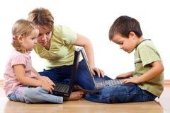 Miúdos que usam portáteis sob a supervisão adulta imagens de stock royalty free