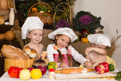 Miúdos vestidos como o cozimento dos cozinheiros chefe Fotografia de Stock Royalty Free