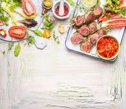 Mięśni skewers z świeżymi ziele, pikantność i warzywo składnikami dla, grilla lub kucharstwa Przygotowanie na lekkim drewnianym t Zdjęcia Stock
