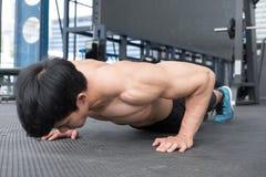 Mięśnia mężczyzna podnosi w gym robić pcha bodybuilder męski pracujący out ja Zdjęcie Royalty Free