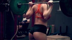 Mięśniowa kobieta pracująca w gym udźwigu ciężarach out