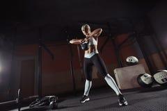 Mięśniowa młoda sprawności fizycznej kobieta podnosi ciężar w gym Zdjęcia Royalty Free