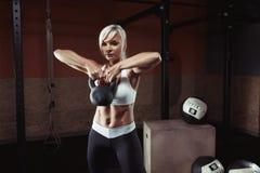 Mięśniowa młoda sprawności fizycznej kobieta podnosi ciężar w gym Obrazy Stock