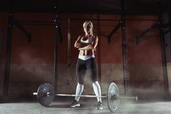 Mięśniowa młoda sprawności fizycznej kobieta podnosi ciężar w gym Obraz Stock