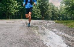 Mięśniowe łydki dysponowany męski jogger szkolenie dla przecinającego kraju lasowego śladu ścigają się w deszczu na natura śladzi obraz stock