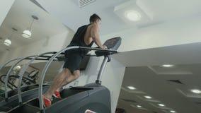 Mięśniowego mężczyzna poruszający up schodki trenuje aparat w gym zbiory