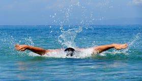 Mięśniowego młodego człowieka pływaccy motyli przełazy zdjęcie stock
