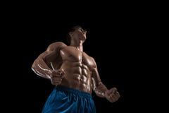 Mięśniowej i dysponowanej młodej bodybuilder sprawności fizycznej samiec wzorcowy pozować nad czarnym tłem Obrazy Stock