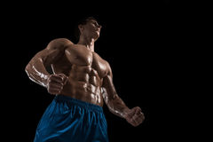 Mięśniowej i dysponowanej młodej bodybuilder sprawności fizycznej samiec wzorcowy pozować nad czarnym tłem Obraz Stock