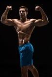 Mięśniowej i dysponowanej młodej bodybuilder sprawności fizycznej samiec wzorcowy pozować nad czarnym tłem Obraz Royalty Free