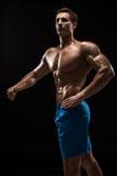 Mięśniowej i dysponowanej młodej bodybuilder sprawności fizycznej samiec wzorcowy pozować nad czarnym tłem Zdjęcie Royalty Free