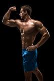 Mięśniowej i dysponowanej młodej bodybuilder sprawności fizycznej samiec wzorcowy pozować nad czarnym tłem Obrazy Royalty Free