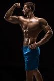 Mięśniowej i dysponowanej młodej bodybuilder sprawności fizycznej samiec wzorcowy pozować nad czarnym tłem Zdjęcie Stock