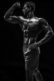 Mięśniowej i dysponowanej młodej bodybuilder sprawności fizycznej samiec wzorcowy pozuje ove Zdjęcia Royalty Free
