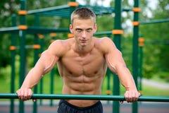 Mięśniowej mężczyzna praktyki uliczny trening w plenerowym gym Obrazy Royalty Free